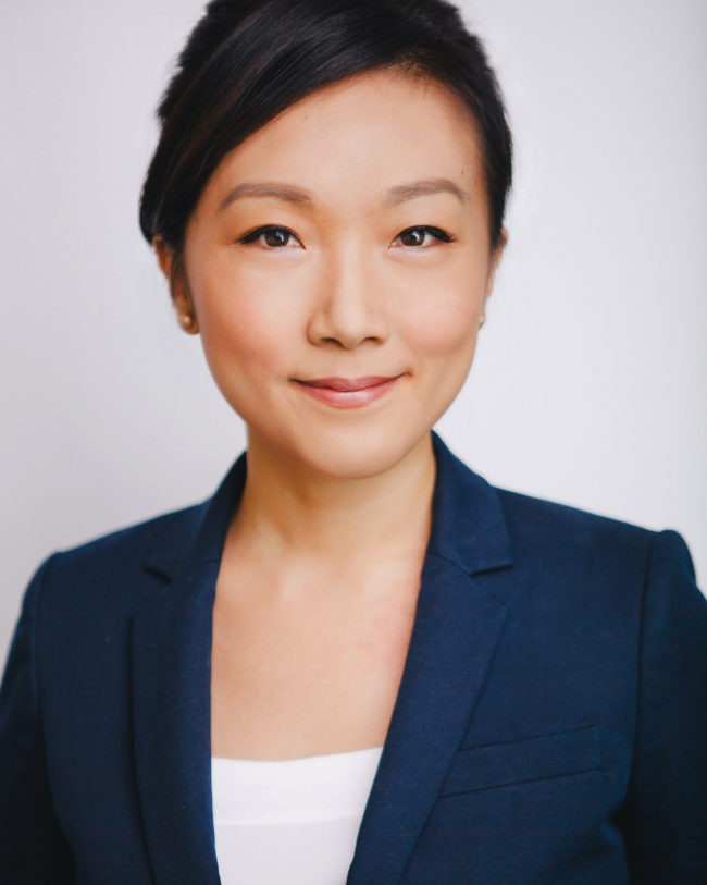 asian woman in a suit with a subtle smile