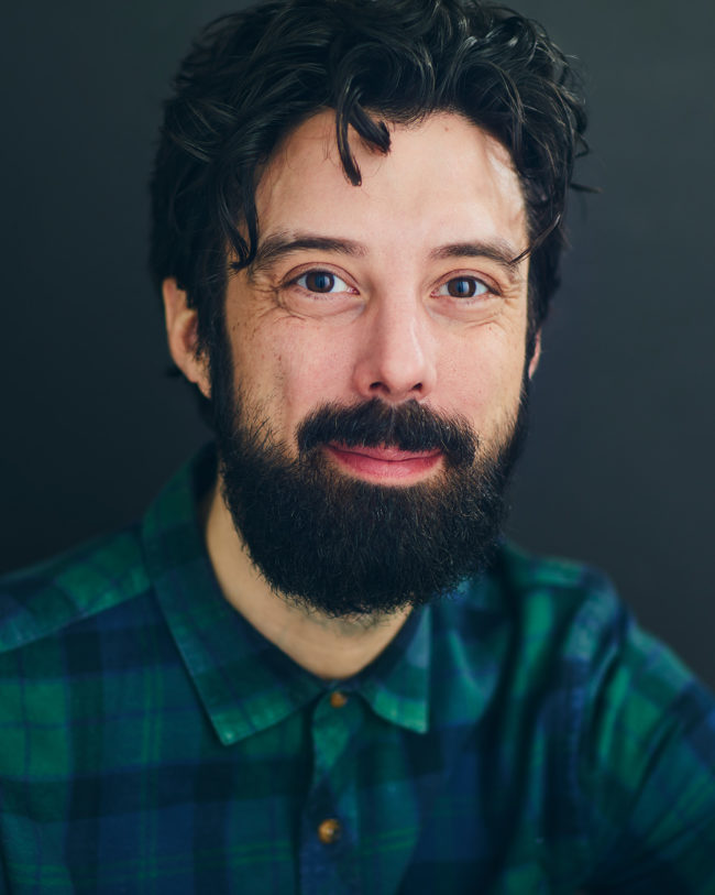 bearded man smiling in plaid shirt