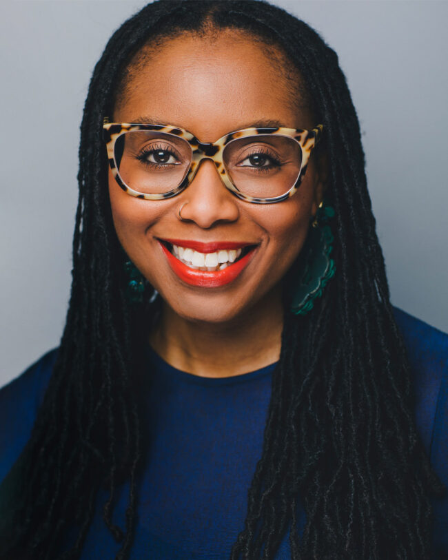 black woman with glasses and a big smile